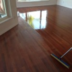 Brazilian Cherry Wood Floor getting Bona Polyurethane coating after screening.