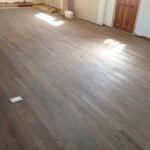 Applying classic gray DuraSeal stain to wood floors