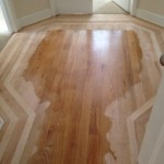 Inlaid wood floor being sanded for refinishing