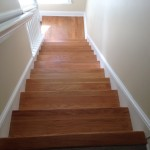 View from the top of wood stairs and landing to be refinished by sanding and staining