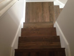 Detail view of stair treads sanded and stained to match new European White Oak wood floors