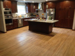 View of new Kitchen Cabinets and Island by Horn Builders, on solid Red Oak flooring repaired by Dan's Floor Store