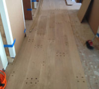 Pegged look white oak flooring planks being installed