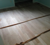 Installing wood flooring with adhesive and flooring straps