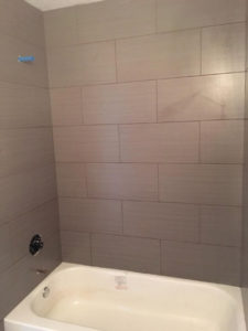 Wood look tile installed - tub & shower surround