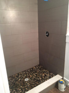 Wood look tile on standup shower walls with river rock floor