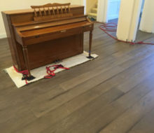 Family piano on carpet on new French Oak wood flooring