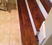 Several stained and finished Birch stair treads, at the bottom of the staircase