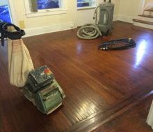 Drum floor sander and vacuum on old white oak flooring for refinishing