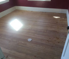 Edge hand scraping old heart pine wood flooring after sanding