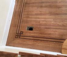 Face nailed white oak flooring corner with walnut strip border after refinishing
