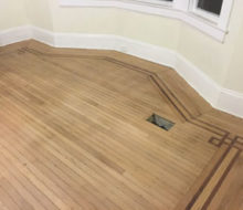 Face nailed white oak flooring with walnut strip border after sanding and hand scraping