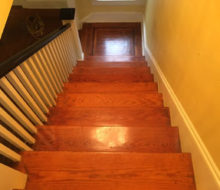 Old heart pine wood stair treads and white oak wood landing with walnut strip border, before refinishing