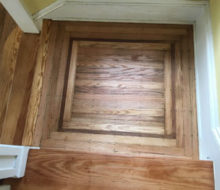 Old heart pine stair treads and face-nailed white oak landing with walnut strip border after refinishing