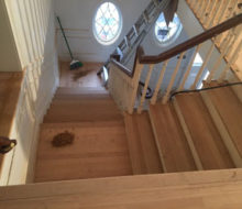 Sanding and hand scraping red oak wood stair treads and landing