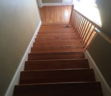 Old, yellowed wooden stair treads and red oak wood flooring prior to refinishing