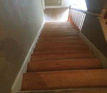 Whitewashed refinished wooden stair treads and red oak wood flooring.