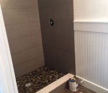 Installed tile shower walls with flat river rock floor