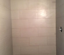 Installed tile shower walls with seat/shelf and flat river rock floor