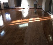 Applying finish to solid red oak plank flooring with walnut pegs