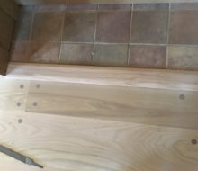 Sanded walnut pegged red oak plank flooring to tile threshold