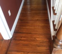 Refinished and restored old heart pine plank flooring - hallway