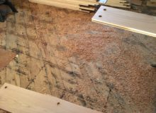 Wood chips on subfloor, from peg hole drilling
