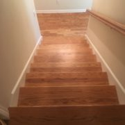 Refinished wooden staircase, rail, and red oak flooring