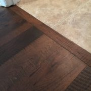 Header board between new engineered Hickory hardwood flooring and tile