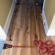 Installing wide Hickory flooring with flooring straps.