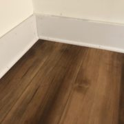 Detail of new baseboards and shoe molding, with Luxury Vinyl Plank flooring