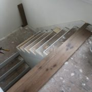 Installing engineered White Oak hardwood flooring stair treads.